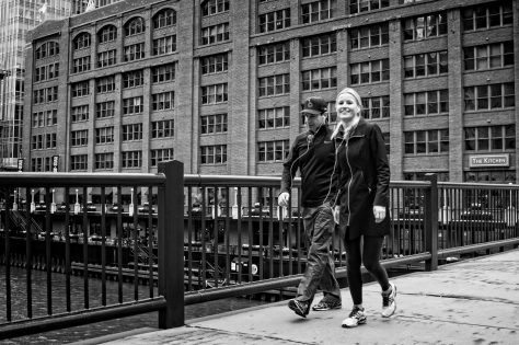 Over the Chicago River, in front of the Merchandise Mart, a couple walks together.