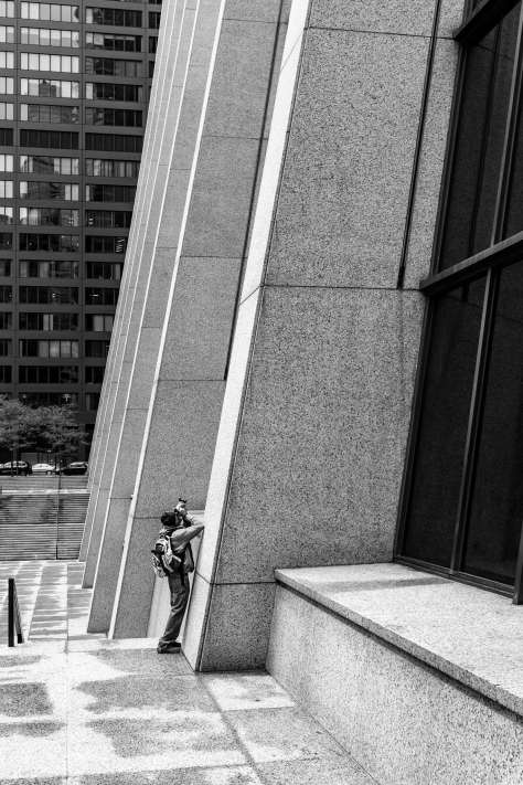 A photographer looking up the big curves of the Chase Tower in Chicago.